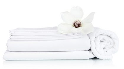 Stack of clean bedding sheets and towels isolated on white